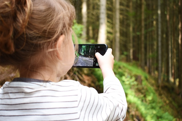 drobná dívka fotografující přírodu